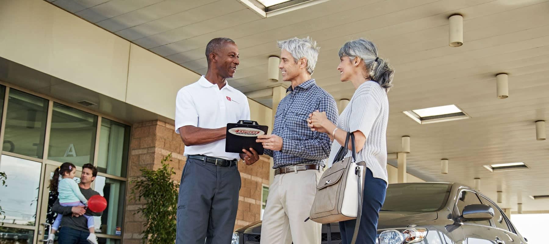 service technician speaks with older couple