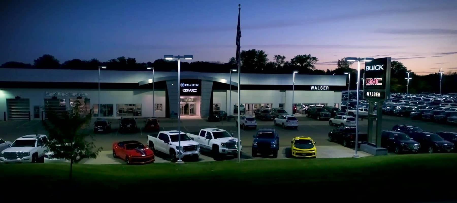 An exterior shot of a Buick GMC dealership at night