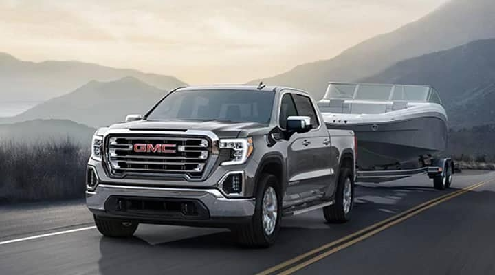 GMC truck pulling boat on highway