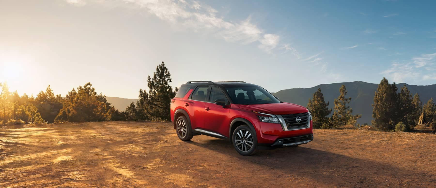 SEO image of Nissan Red SUV on mountaintop