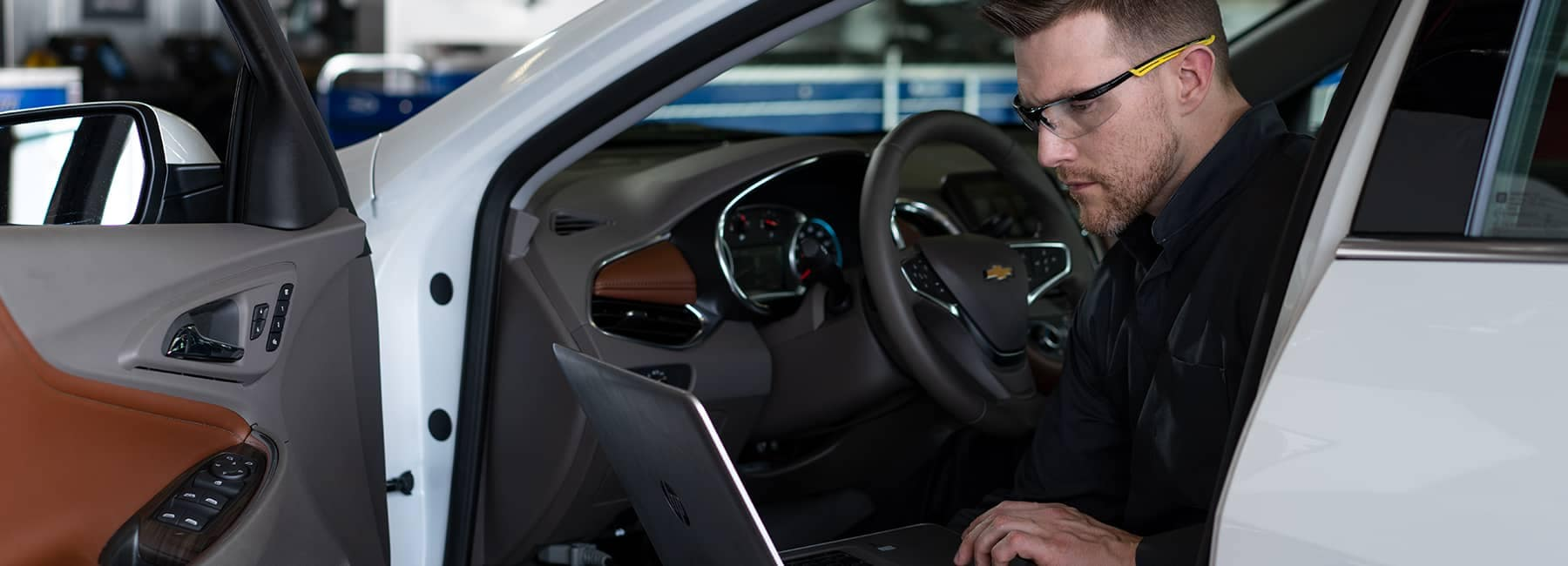 Service technician inside a car looking at his laptop.