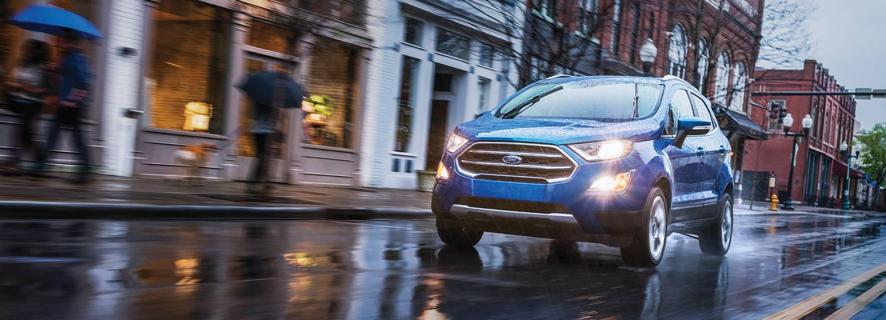 Blue 2021 Ford EcoSport driving on a rainy suburban town street