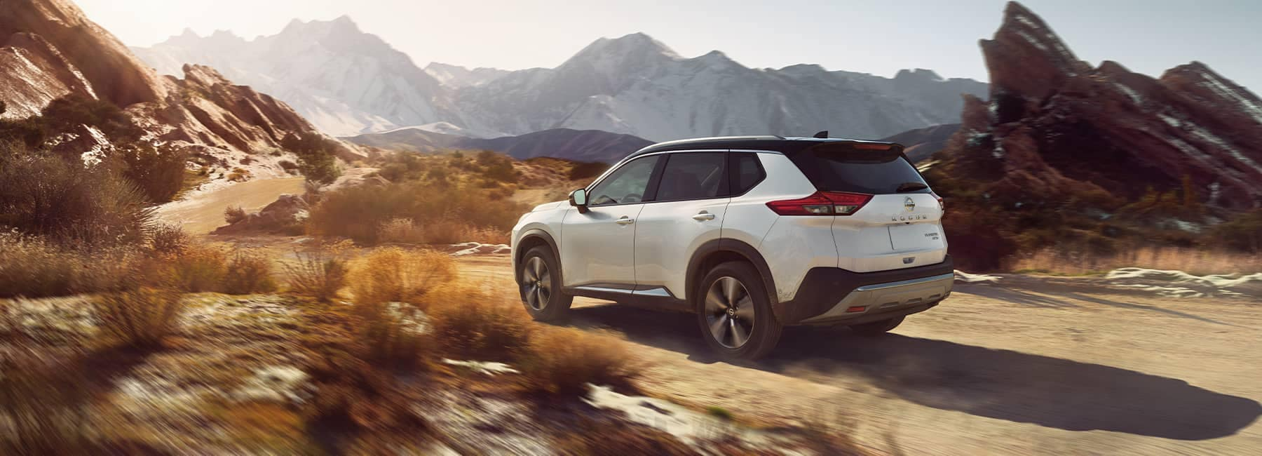 A 2021 White Nissan Rogue driving on a mountain pass