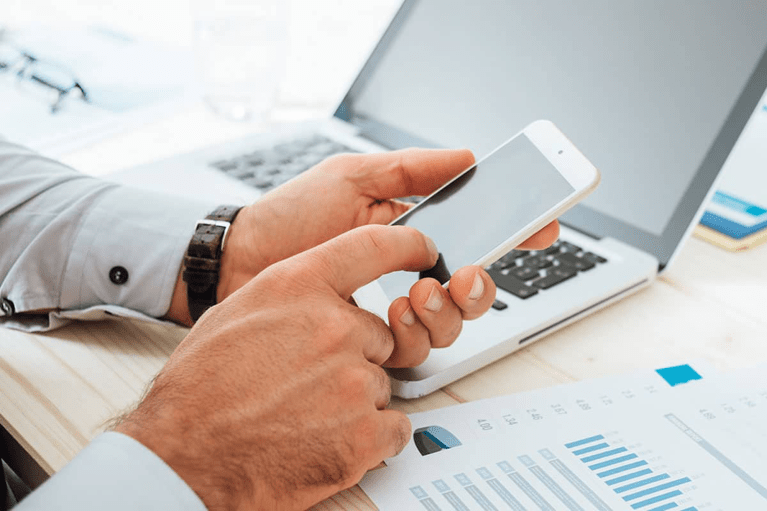 man calculates finances with smartphone