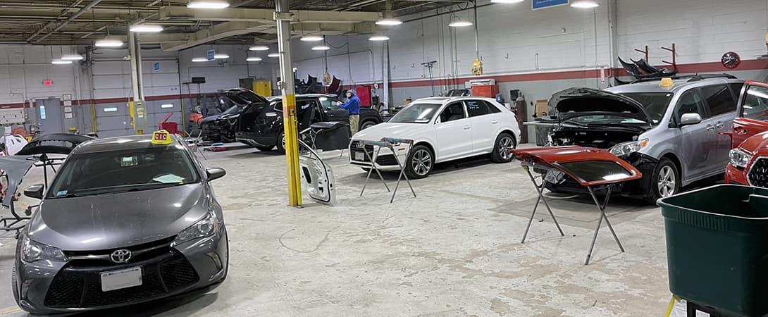 technicians work on cars in body shop