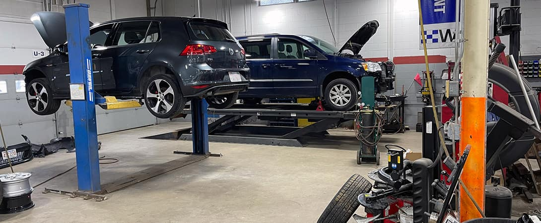 two cars up on jacks in auto body shop