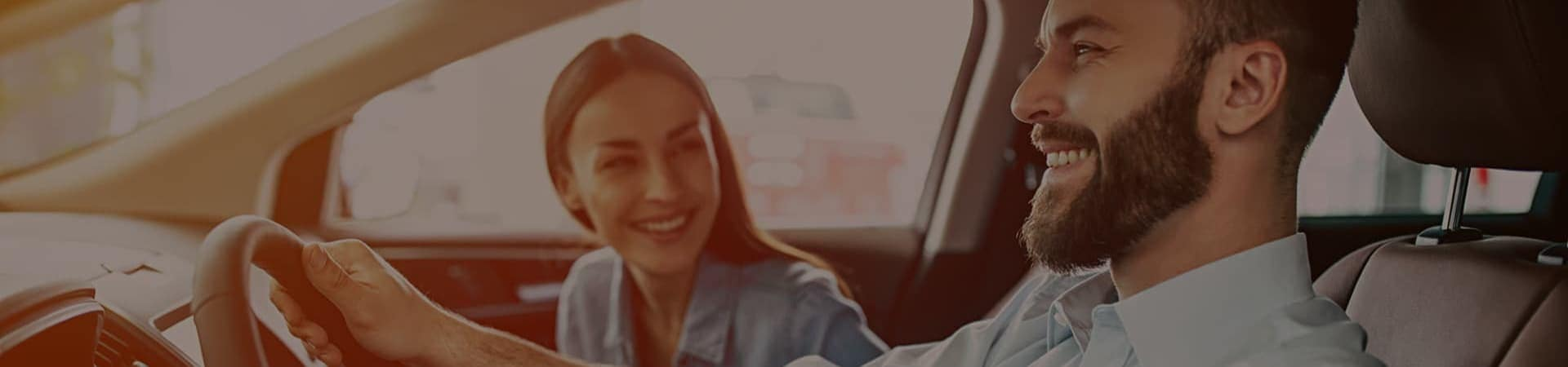 Woman in passenger seat smiling while looking at man driving the vehicle