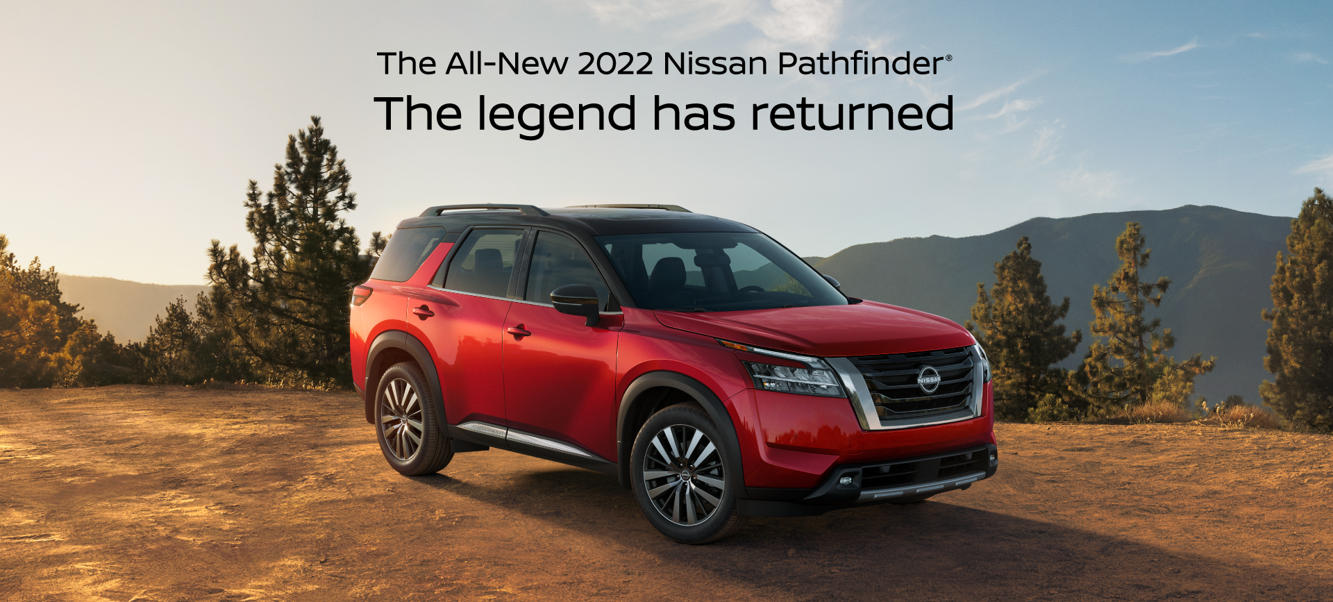 Nissan Pathfinder on clay road with green, mountainous backdrop