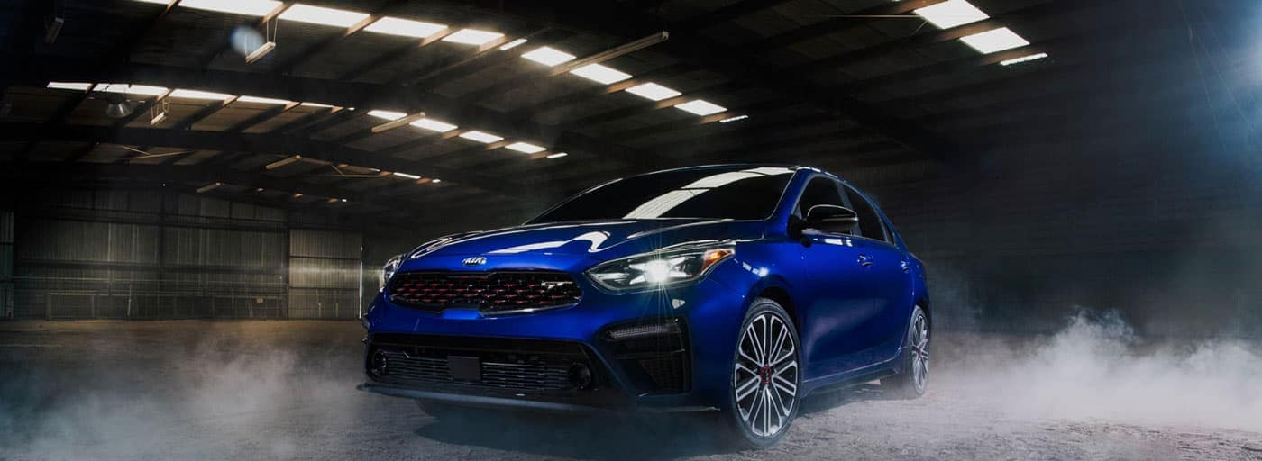 Blue Kia Sedan driving through a dark and smokey tunnel
