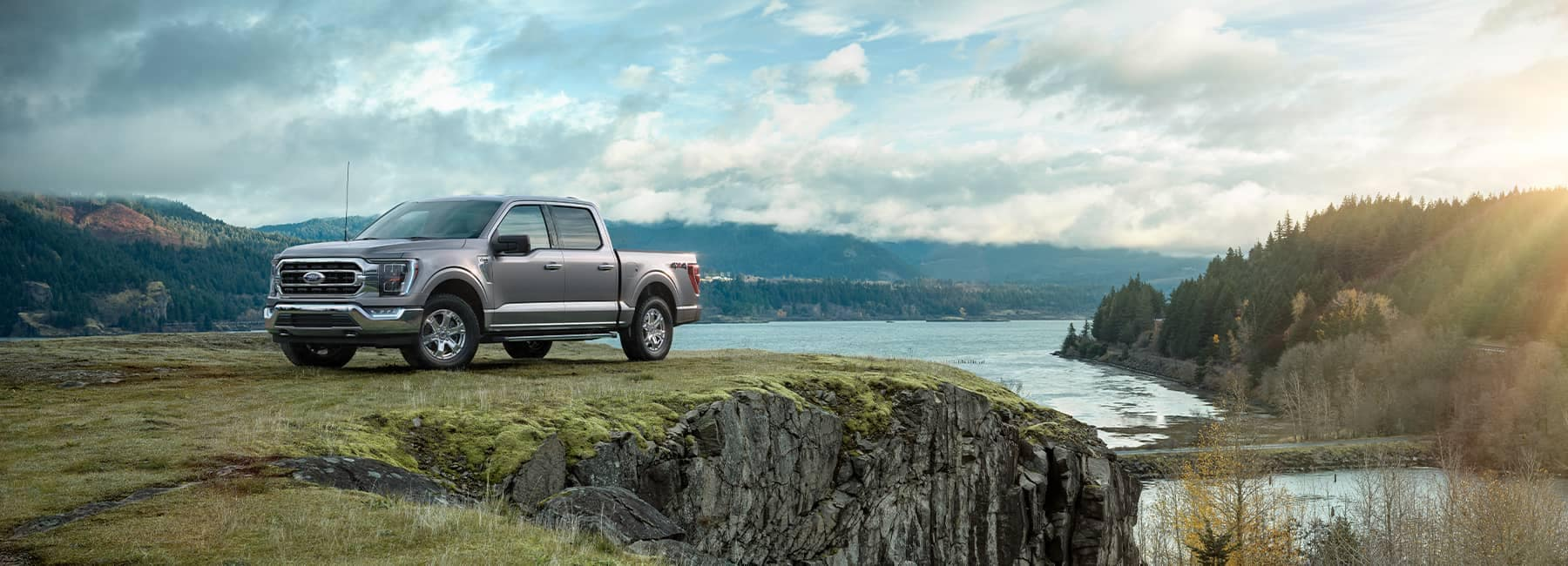 Silver 2021 Ford F-150 parked on a cliff overlooking a river