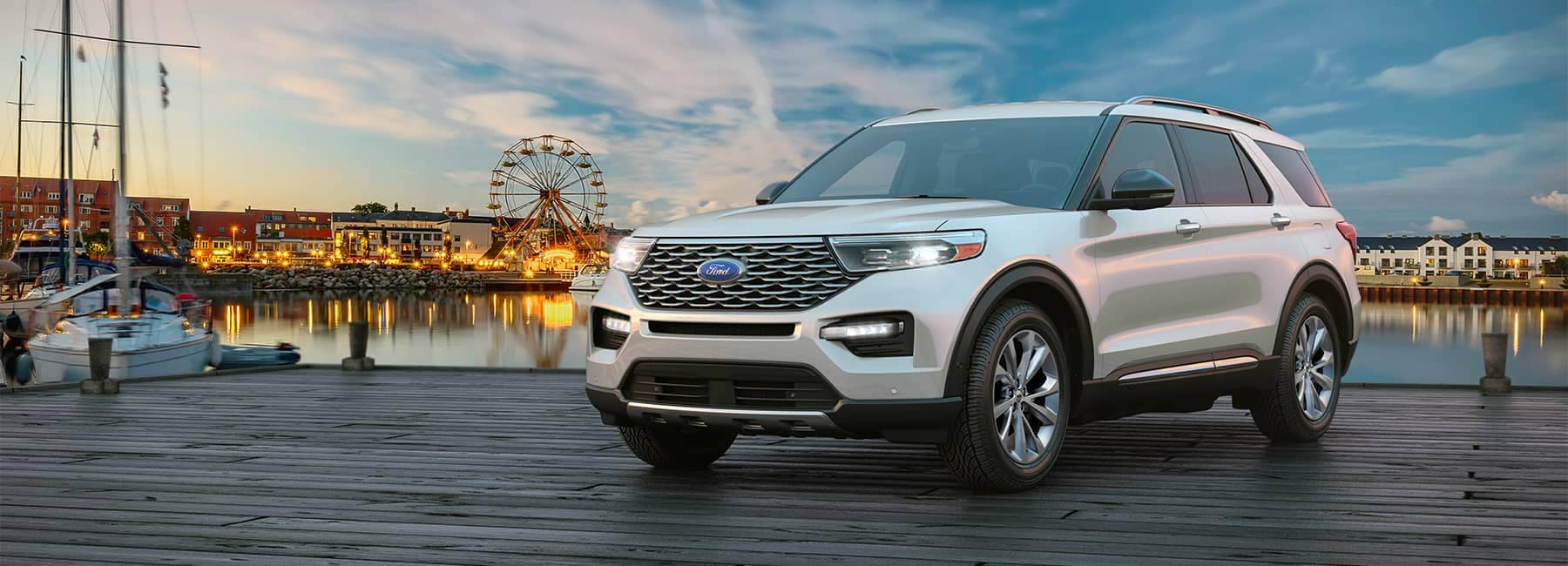 White 2021 Ford Explorer parked on a boardwalk with a ferris wheel in the background