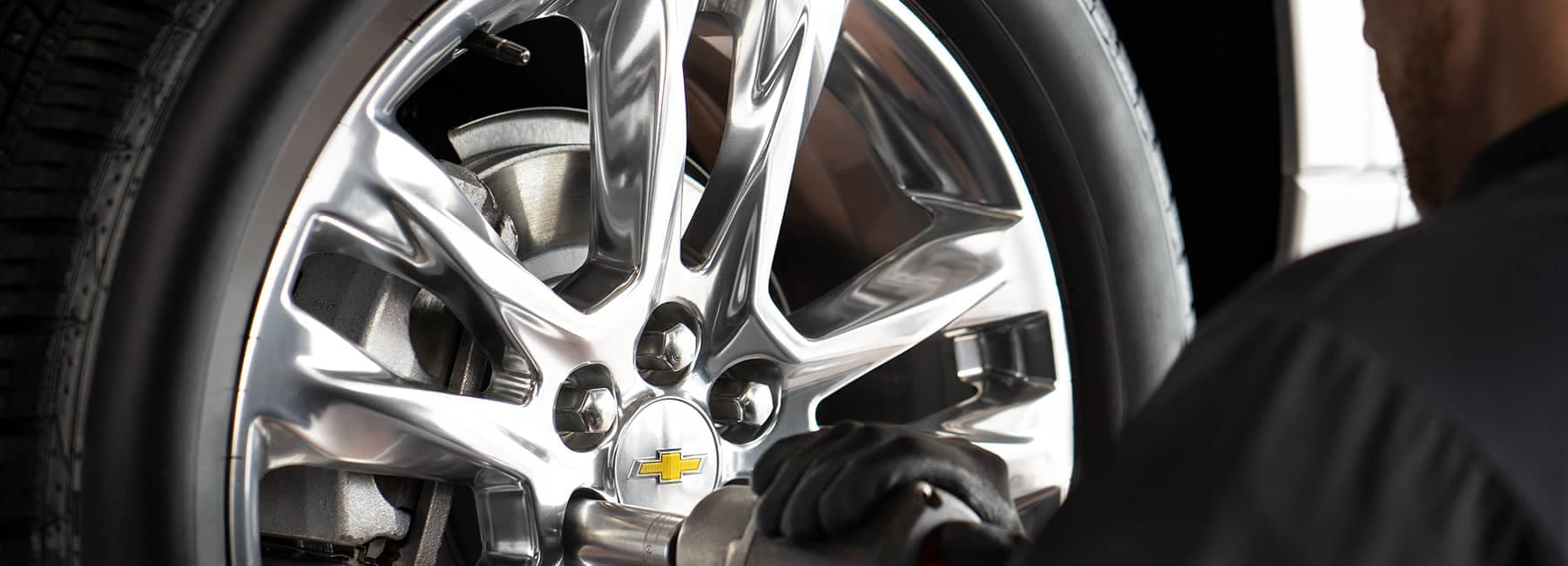 service technician tightens bolts on Chevy wheel