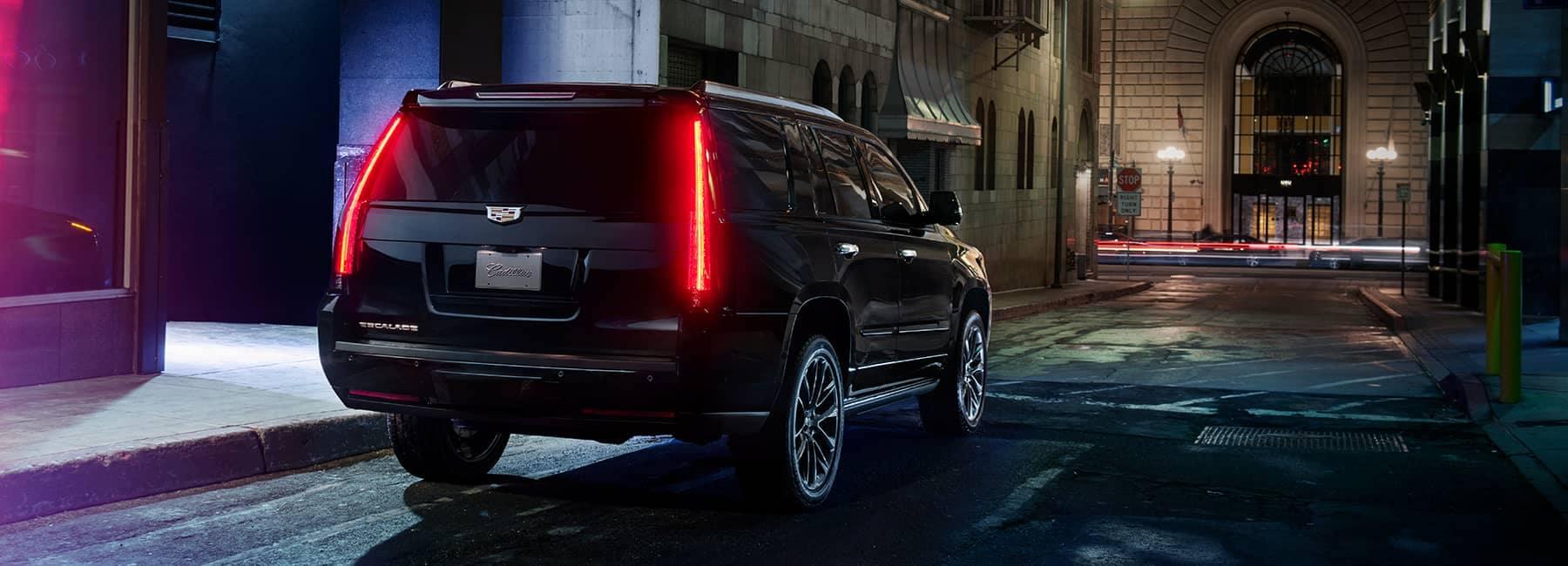 cadillac Black Cadillac Escalade parked in a city at night