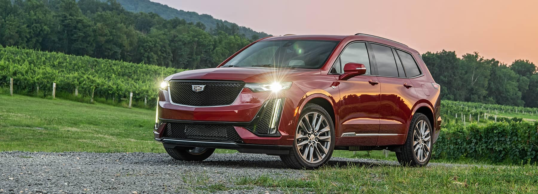 Red Cadillac XT6 Parked on a dirt road at dusk